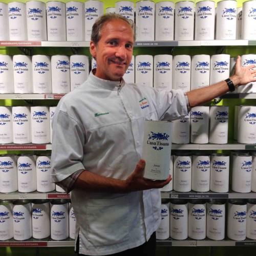 Christophe-Chevalier- pharmacien-Herboriste-CasaTisana en photo devant un rayon de boites de tisanes Casatisana